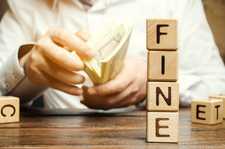 man holding a wad of paper money notes with 'fine' spelt in blocks next to him