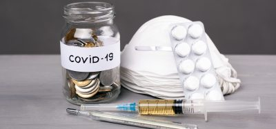 a pile of face masks next to a syringe, a thermometer and a jar of coins labelled 'COVID-19'