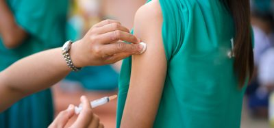 young girl receiving a vaccine from a volunteer