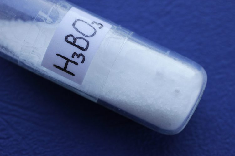 crystallised boronic acid in a test tube with chemical formula H3BO3 on front