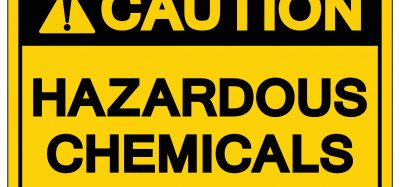 yellow warning label reading 'caution hazardous chemicals' in black