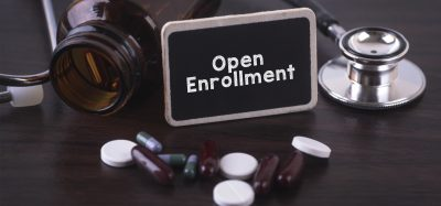 medicine bottle with stethoscope and black and white tables surrounding a sign saying 'open enrollment'