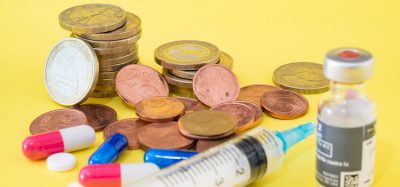 vial of vaccine with syringe and pills next to stacks of euro coins