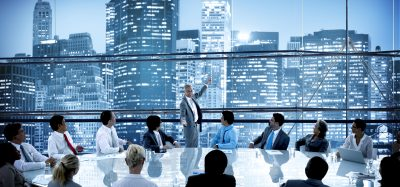 boardroom with huge table surrounded by a diverse group of people