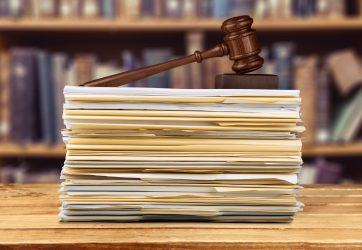 stack of legislation documents with court gavel on top