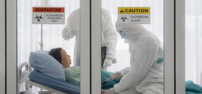 patient in a hospital bed with doctors in personal protective equipment behind glass doors with quarantine stickers on