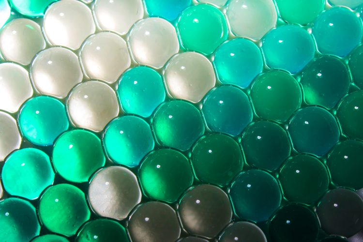 blue and green hydrogel balls in rows