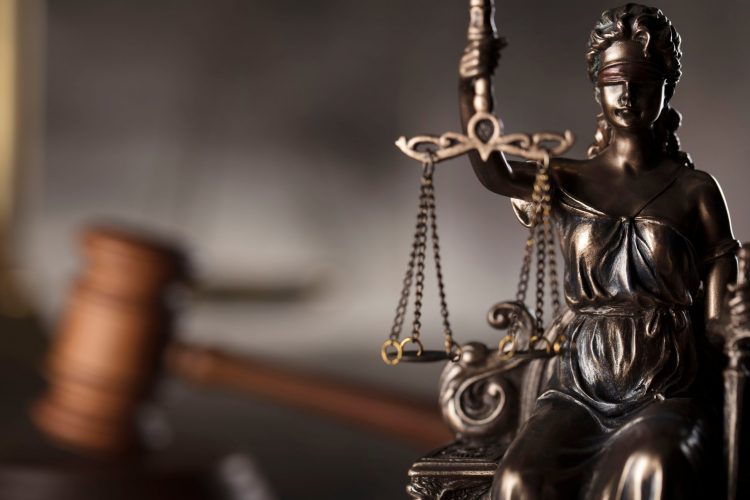 Lady Justice holding scales with gavel in the background