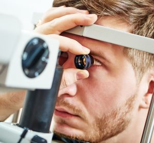 man undergoing an eye examination by an ophthalmologist
