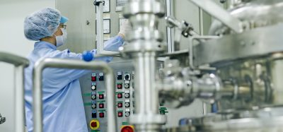 pharmaceutical factory worker operating machine