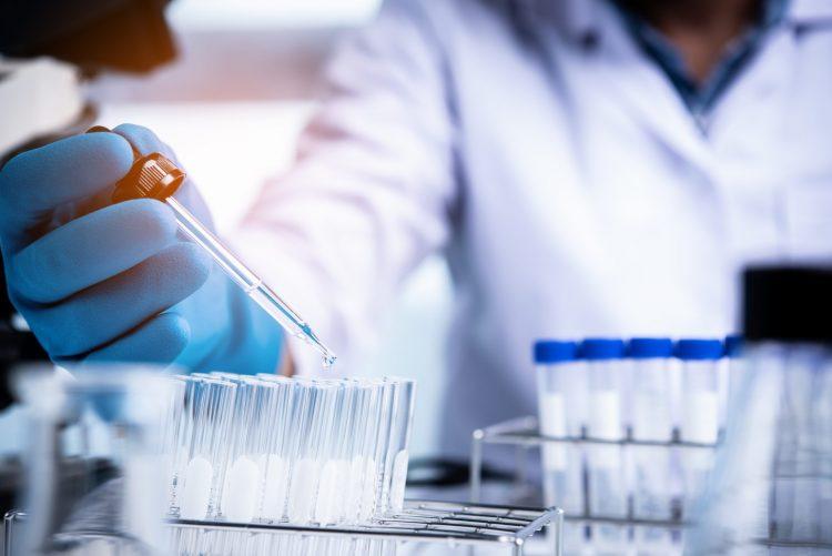 scientist pipetting liquid into a test tube