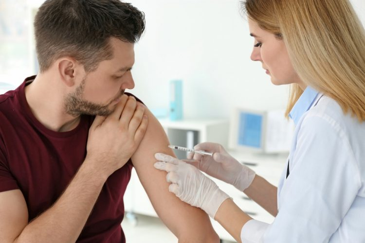 Doctor vaccinating man