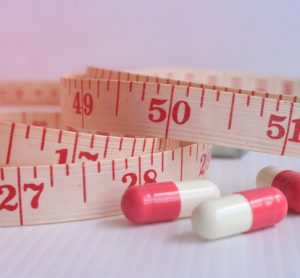 Pills next to tape measure